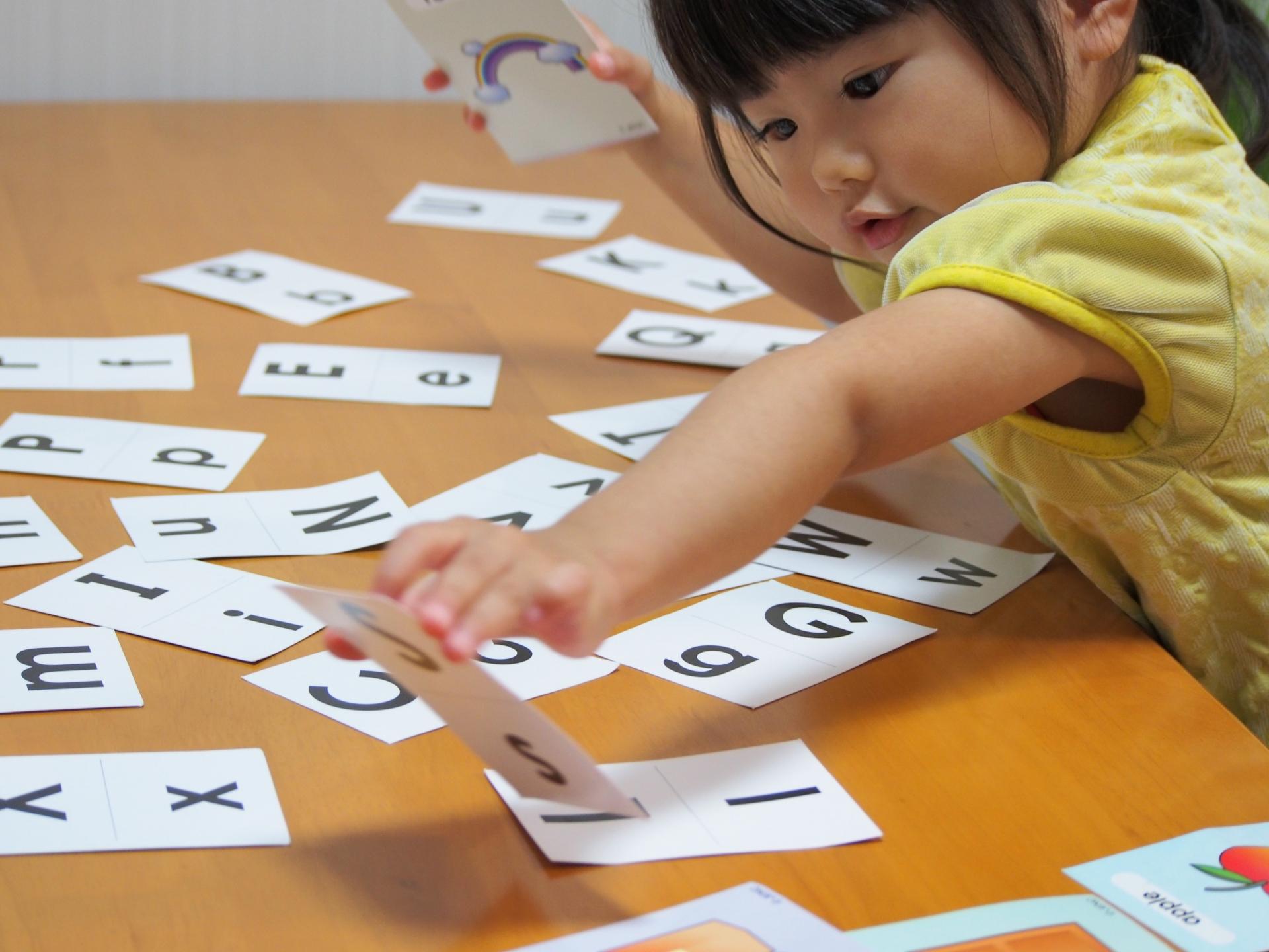 キッズ英会話レッソンで女の子は英語の文字を覚えています。